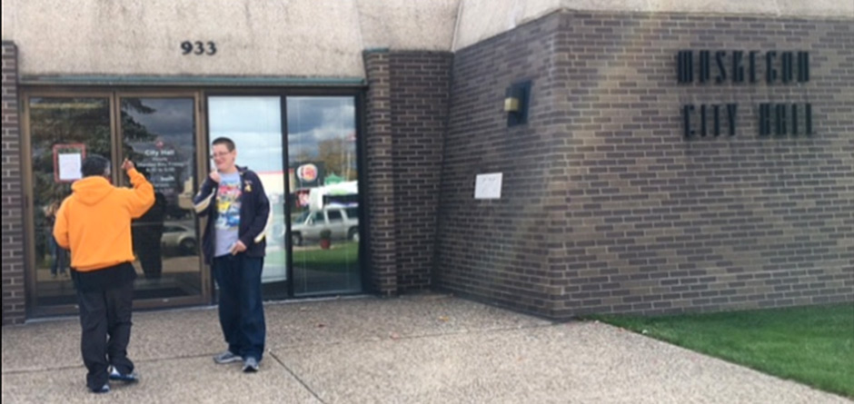 Young Person outside Muskegon City Hall