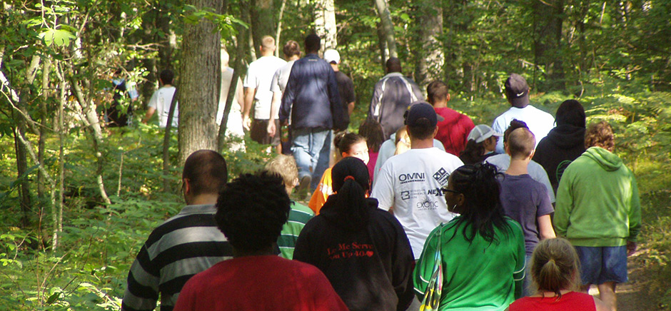 Campers Hiking in Woods